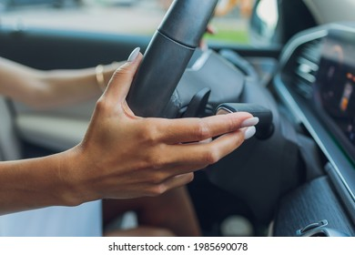 Woman's hand switches the lobes of the gear selector on the steering wheel. Hand is switching car gear lever, close up shot of a manual gear changing paddle on a car's steering wheel.