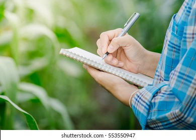 Woman's hand take notes with a pen on a notebook in agriculture garden.