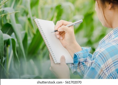 Woman's hand take notes with a pen on a notebook in agriculture garden
