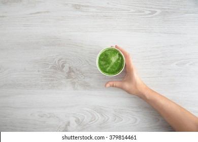Woman's hand takes away paper glass with prepared japanese organic premium matcha tea latte. On white wooden table. Top view