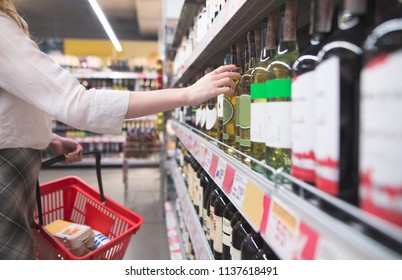 Woman's hand takes a bottle of wine from the shelf at the supermarket. Purchase of wine in the alcohol department of the store. Alcohol Concept. The girl buys a bottle of wine at the supermarket.