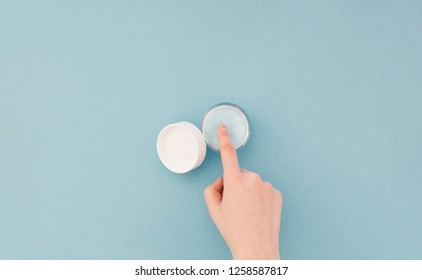 Woman's hand takes a finger from a cream bottle of skin care cream. Skin care. Hands and cream jar are isolated on a blue background. Flay lay
