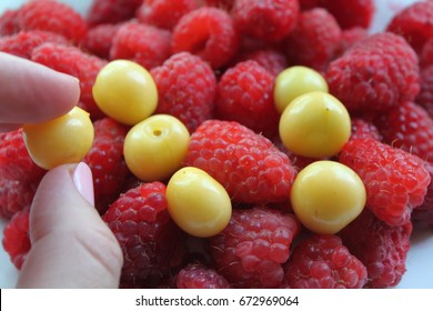 The woman's hand takes yellow cherry and raspberry