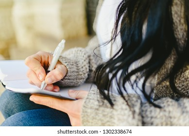Woman's hand taking notes in her notebook with pen, sitting.