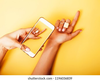 womans hand taking picture of her new manicure with fashion jewe
