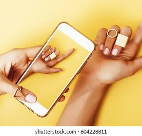 womans hand taking picture of her new manicure with fashion jewellery on her phone, girls stuff concept