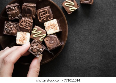 Woman's hand taking a piece of chocolate from the brown plate on the dark table. Enjoying a candies. Sweets concept. Mock up for candies offers as advertising or other ideas. Empty place for a text.