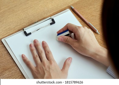 A woman's hand that erases the letters on the document with an eraser