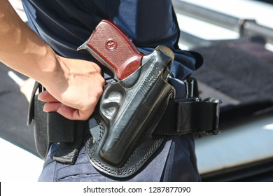 A woman's hand touches a body and a gun. Woman with a gun. Woman policemen with gun in a black holster. Makarov gun in a police holster. Profession, a job that saves lives. Profession police officer.