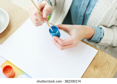 Woman's hand touching blue paint with brush, drawings, paints on wooden table, white manicure, mock up, flat lay, point of view.