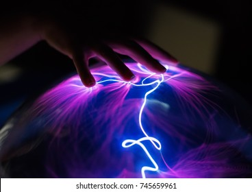 Woman's hand touching plasma globe.