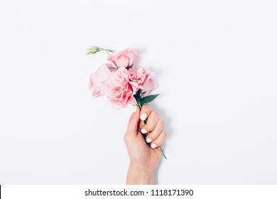 Woman's hand with trendy manicure holding small bouquet of pink flowers in the center of white background, top view. Minimal flat lay composition of beautiful blooming eustomas with green leaves.