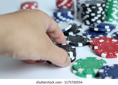 The woman's hand trying to grab the casino chip.