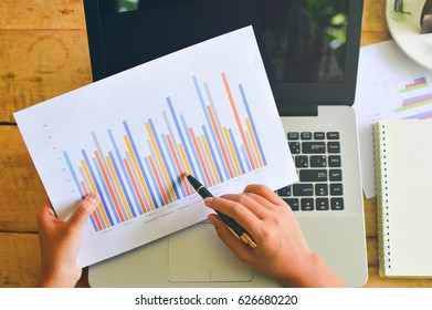 Woman's hand typing on laptop computer. Business report, mobile phone and business summary laid on desk.