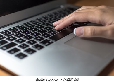 Woman's hand typing on laptop computer keyboard