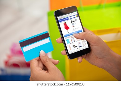 Woman's Hand Using Credit Card For Shopping Online On Smartphone
