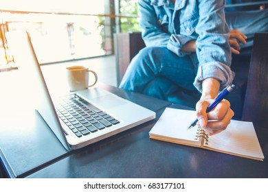woman's hand using laptop and writing in notepad in an office.