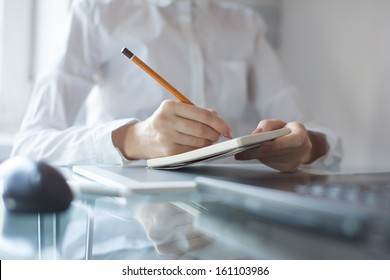 Woman's hand using a pencil noting on notepad