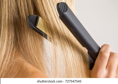 Woman's hand using straightener on her blonde hair on the gray background. Cares about a smooth, beautiful hair. Beauty salon concept.