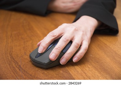 Woman's hand using a wireless computer mouse. Focus is on the front of the mouse / end of the fingers.