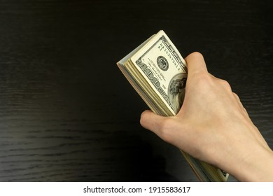 Woman's hand with a wad of hundred-dollar bills on a dark background close-up with copy space