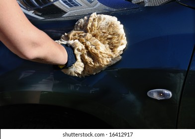 woman's hand washing a car using a natural sheepskin washmitt