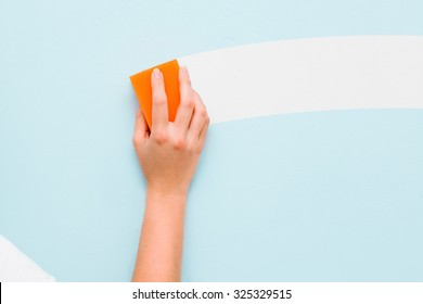 Woman's hand washing wall by the sponge
