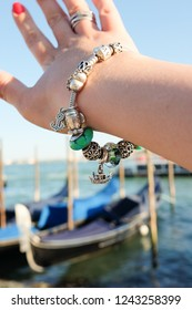 Woman's hand wearing beautiful bracelet with gondola charm over the gondolas on Venice, Italy