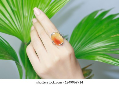 Woman's hand wearing an carnelian gemstone ring