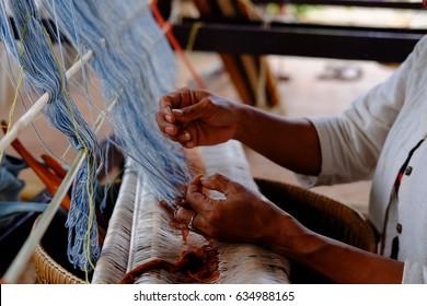 Woman's hand weaving cotton on manual loom