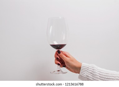 Woman's hand in a white sweater holding a glass of red wine. Minimalist concept.