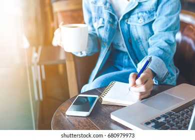Woman's hand working in office,She is taking notes and raising a cup of coffee.