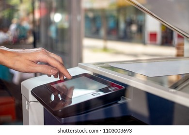 Woman's hand working on the copier's touchscreen on a street copy center