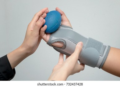 Woman's hand with wrist support squeezing a soft ball for hand exercise ,rehabilitation hand
