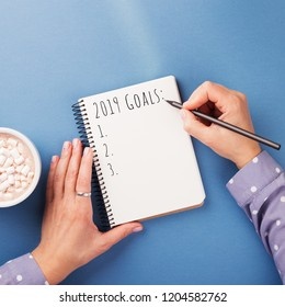 Woman's hand writing 2019 Goals in notebook on the blue background. Top view.