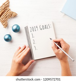 Woman's hand writing 2019 Goals in notebook on the wooden table. Top view.