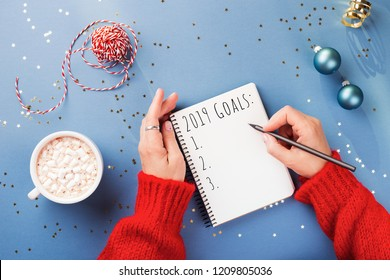 Woman's hand writing 2019 Goals in notebook decorated with Christmas decorations on the blue background. Top view.