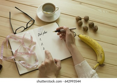 Woman's hand writing diet plan on diary