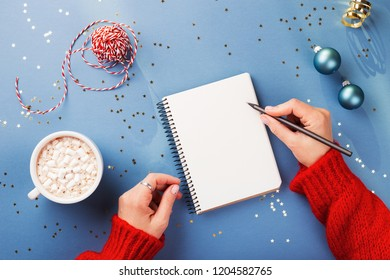 Woman's hand writing in notebook decorated with Christmas decorations on the blue background. Top view.