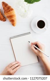 Woman's hand writing in notebook on white wooden table. Working place and planning concept, morning time, top view.