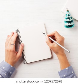 Woman's hand writing in notebook on the wooden table. Top view.