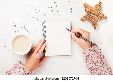 Woman's hand writing in notebook on the white wooden table. Top view.