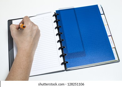 Woman's hand writing on agenda/Managing calendar