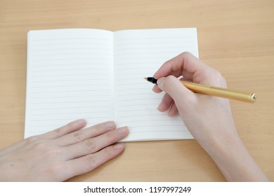 Woman's hand is writing on a blank notepad with a pen on a wooden