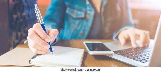 A woman's hand is writing on a notepad with a pen and a phone with a laptop.Web banner.