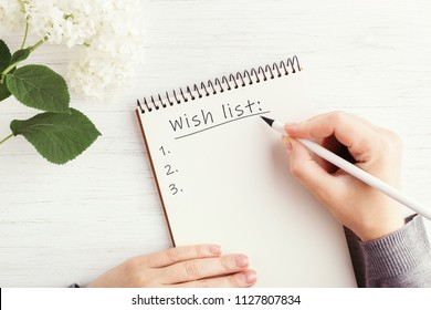Woman's hand writing Wish list in notebook on white wooden table. Working place and planning concept, top view.
