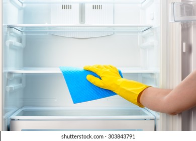 Woman's hand in yellow rubber protective glove cleaning white open empty refrigerator with blue rag