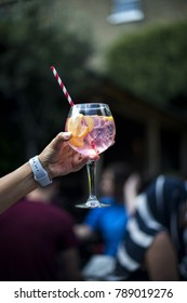 Woman's handing holding a glass of gin & tonic cocktail in a pub garden