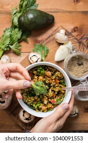 Woman's hands adds a celery leaf on top traditional buckwheat porridge with vegetables with raw tomatoes, mushrooms, garlic, onion, olive oil, and celery. Raw, vegan, vegetarian healthy food concept.
