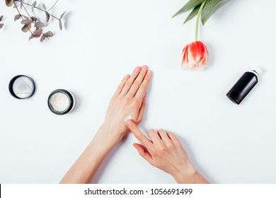 Woman's hands apply cream on skin. The concept of pre-testing cosmetics before use. Top view of female hands among the feminine environment